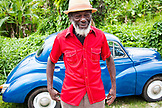 "JAMAICA, Port Antonio. Derrick ""Johnny"" Henry of the Mento band, The Jolly Boys standing by a blue vintage car."