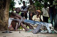 Anti-Balaka-Kämpfer in Bangui, Zentralafrikanische Republik,  verspotten einen Mann (li.), den sie wenige Stunden vorher gefangen haben. Sie werfen ihm Diebstahl vor, das angebliche Diebesgut liegt im Vordergrund. Wenige Minuten nach der Aufnahme wurde der Mann erschlagen.