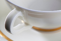 White china cup and saucerwith gold leaf close up.