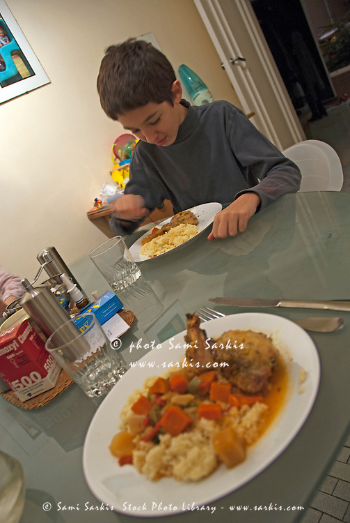 Boy eating dinner at the kitchen table, France.