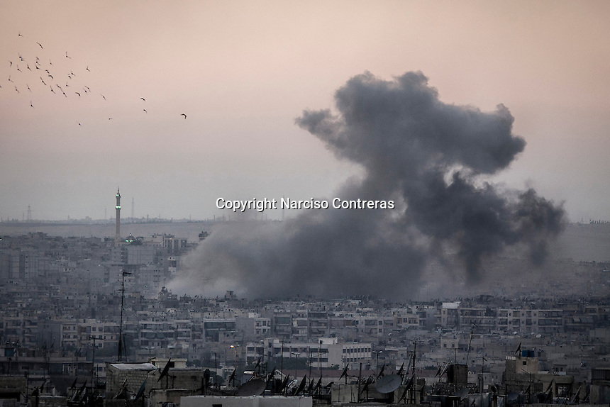 A plumbe rises up to the sky as a combat jet targets a civilian building houses during aircraft shelling upon rebel positions in Bustan Al-Bashar neighborhood at the north of Aleppo City.