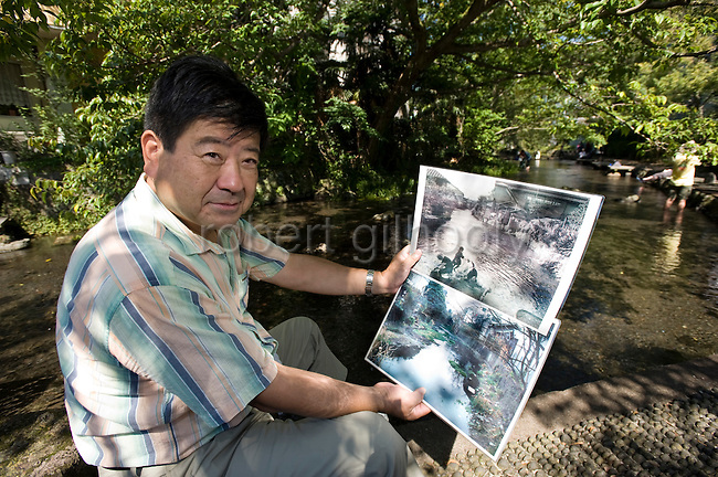 Dr Toyohiro Watanabe holds up photos of how the Genbe River used to be in  in Mishima, Shizuoka Prefecture Japan on 02 Oct. 2012.  Photographer: Robert Gilhooly