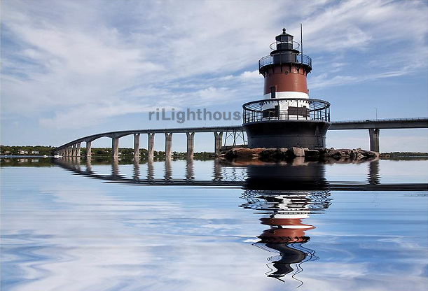 The Jamestown Bridge and Plum Beach Lighthouse are reflected in the calm waters of Narragansett Bay.