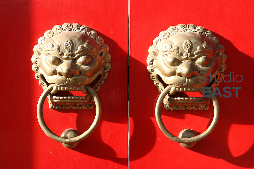 Lions' handles hang on a traditional Chinese door in Beijing, China, on March 18, 2006. Photo by Lucas Schifres/Pictobank