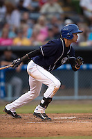 Asheville Tourists shortstop Emerson Jimenez #14 swings at a pitch during a game against the Savannah Sand Gnats at McCormick Field July 17, 2014 in Asheville, North Carolina. The Tourists defeated the Sand Gnats 8-7. (Tony Farlow/Four Seam Images)