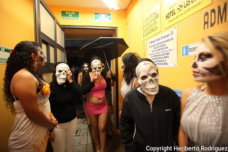 Mexican prostitutes wearing face masks pay homage to their dead comrades during a traditional ofrenda of Day of the Deads in the old neighborhood of La Merced, in the historic center of Mexco City, October 30, 2009. More than one hundred prostitutes celebrate a preHispanic tradition to honor their deads. Photo by Heriberto Rodriguez