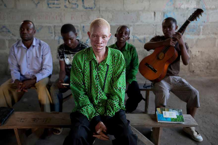 June 26, 2010 - Dar Es Salaam, Tanzania - Augostino Msisi, a 49 year old Tanzanian albino attends a church service at the Tanzania Assembly of Gods church in Dar Es Salaam. Albinism is a recessive gene but when two carriers of the gene have a child it has a one in four chance of getting albinism. Tanzania is believed to have Africa' s largest population of albinos, a genetic condition caused by a lack of melanin in the skin, eyes and hair and has an incidence seven times higher than elsewhere in the world. Over the last three years people with albinism have been threatened by an alarming increase in the criminal trade of Albino body parts. At least 53 albinos have been killed since 2007, some as young as six months old. Many more have been attacked with machetes and their limbs stolen while they are still alive. Witch doctors tell their clients that the body parts will bring them luck in love, life and business. The belief that albino body parts have magical powers has driven thousands of Africa's albinos into hiding, fearful of losing their lives and limbs to unscrupulous dealers who can make up to US$75,000 selling a complete dismembered set. The killings have now spread to neighboring countries, like Kenya, Uganda and Burundi and an international market for albino body parts has been rumored to reach as far as West Africa. Photo credit: Benedicte Desrus