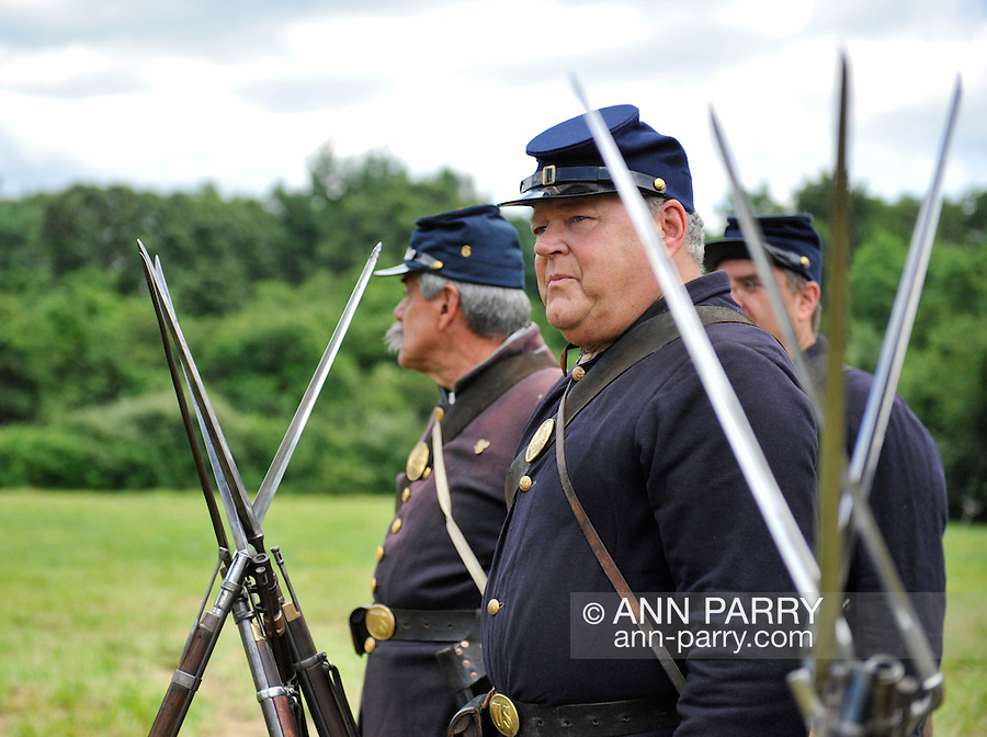 Old Bethpage, New York, USA - July 21, 2012: Rifles with attached bayonets are in foreground, as federal re-enactors assemble for military maneuvers at Camp Scott, a Union Army training camp, at Old Bethpage Village Restoration, to commemorate 150th Anniversary of American Civil War, on Saturday, July 21, 2012.