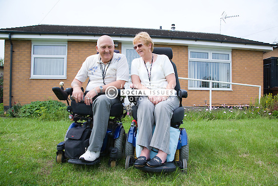 Wheelchairusing couple user outside their house; concrete ramp and grab rails in the background,