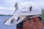 08815-C. Salmon Fly (a.k.a., Giant Stone Fly) patterns are stuck in a fly fisherman's cap on the Henry's Fork of the Snake River, Idaho