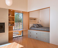 A bedroom with storage drawers below is set in a recess, next to which is a built-in desk and shelving arrangement.
