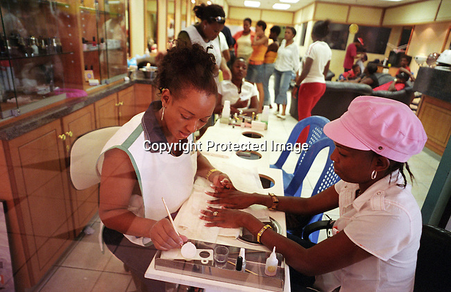 "African,women,black,manicure,beauty,middle-class,.Unidentified women having their nails and hair done at ""Romeo & Julieet"" hair salon on December 25, 2003 at South Gate, a shopping mall, outside Soweto, South Africa. There's a slowly growing black middle-class in townships such as Soweto, and people start to own their first house, car. At South Gate, one of the busiest malls in the country, thousands of mainly black South Africans spend more money on furniture, electronic equipment and other goods. A majority of South Africans live in poverty, but for a growing number of people positive changes has happened since the fall of Apartheid and the start of democracy in the country in 1994. .©Per-Anders Pettersson/iAfrika Photos......"