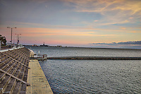 This is the sea wall that run down a good portion of Corpus Christi bay as the sunrise was just beginning to color the sky in the early morning.  You can see the USS Lexington in the distance and breakers along the bay along the seashore in this quaint seascape along the texas coast.