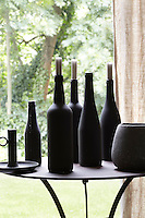 An assortment of black bottles is transformed into candlesticks and displayed on a circular iron table in the dining area