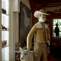A 1940's concrete cowboy and his dog stand in the office area of the open-plan living room