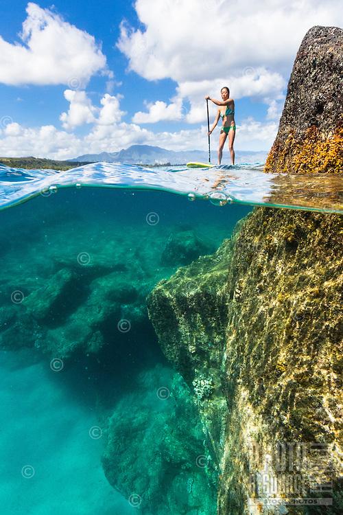 A woman standup paddles in the calm waters of Waimea Bay, North Shore, O'ahu.
