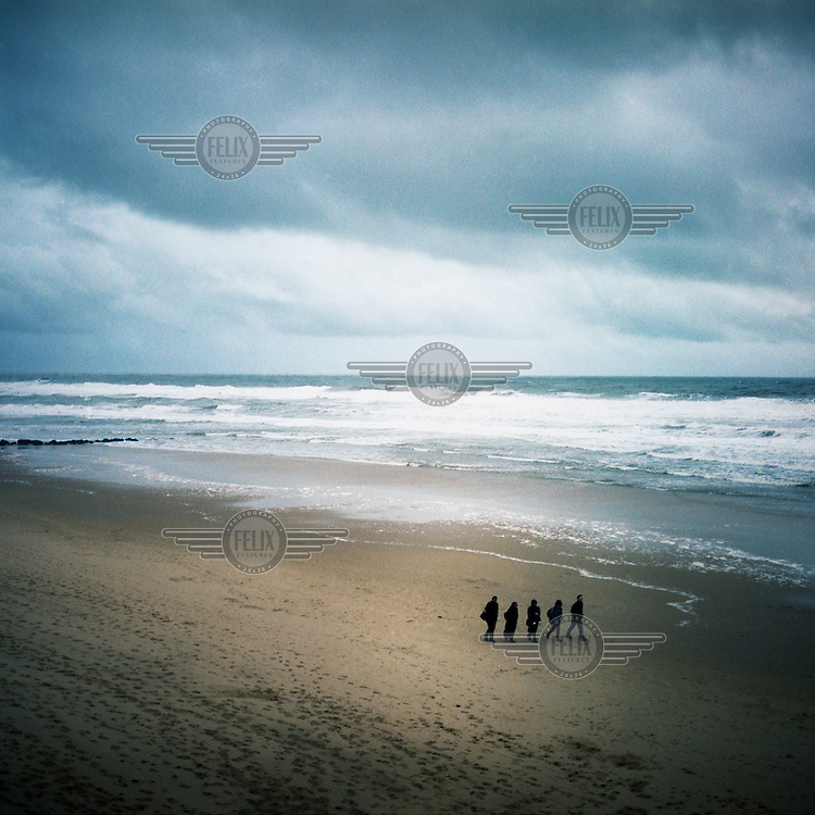 People stroll on the beach at Lacanau-Ocean, a resort along the Cote d'Argent on the Atlantic ocean.