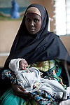 HABASWEIN, KENYA - JULY 4: Amina Yare Isak holds her 3 month old daughter Umi Adan Olow on July 4, 2011 in a ward at the hospital in Habaswein, Kenya. Earlier she went to a Save the Children outreach site in the location to weigh and check her child. The child weighed only 1,7 kilograms. Umi was referred to the hospital in nearby Habaswein. The team examined about thirty children, among them some severely malnourished. Umis's mother brought her to the outreach site. The child has been sick a lot since birth. Amina Yare Isak, her mother, has two other children in the Save the Children nutrition program. The mother blames the drought for her children's sickness. Her livestock was finished and the lack of milk made her children malnourished. Two successive poor rains, entrenched poverty and lack of investment in affected areas have pushed millions of people into a fight for survival in the Horn of Africa. This is the driest this area have been since sixty years. (Photo by Per-Anders Pettersson)