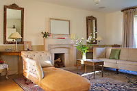 In the living room a pair of antique gilt-framed mirrors above matching console tables flanks the fireplace of Cotswold stone and a comfortably shabby chaise longue has been placed opposite the sofa