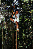 Manaus, Brazil. Fit guide showing how to climb high up a liana during a forest walk. Ecopark.