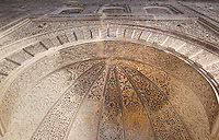 Looking up inside the niche of the mihrab with its intricately carved stucco work in the Al-Attarine Madrasa, a religious school built 1323-25 by the Marinid Sultan Uthman II Abu Said, who ruled 1310-31, in the medina of Fes, Fes-Boulemane, Northern Morocco. The mihrab marks the direction of Mecca. The medina of Fes was listed as a UNESCO World Heritage Site in 1981. Picture by Manuel Cohen