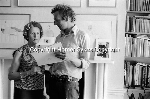 Patrick Procktor artist London 1968. Patrick with his mother Barbara in the Manchester Street flat.He is showing her some of my photographs. On the mantle piece is an image of PP and Gervase, his close friend.
