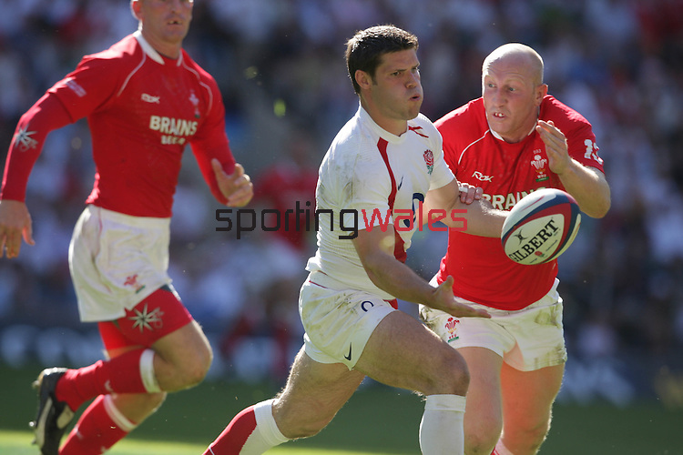 Dan Hipkiss times his pass as Tom Shanklin closes in..Investec Challenge.England v Wales.Twickenham.04.08.07.©Steve Pope.Sportingwales.The Manor .Coldra Woods.Newport.South Wales.NP18 1HQ.07798 830089.01633 410450.steve@sportingwales.com.www.fotowales.com.www.sportingwales.com