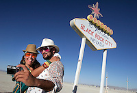 BLACK ROCK CITY, NV - AUGUST 27,2008:  Welcome to Black Rock City. Simone Oliver of San Diego and Eric Weisz of San Francisco take a photograph in front of an art installation, August 27, 2008. The Burning Man Event 2008 kicked into full gear as participants from around the world begin to converge in Nevada for the annual art event. The event, which culminates with the burning of large installation art over the weekend, attracts over 30,000 people annually.