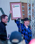 Nate Holland, right, holds up a plaque he received during the Olympic Homecoming  Celebration at Squaw Valley on Friday night, March 21, 2014.