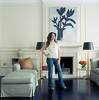 Giulia Azmoudeh stands in front of a painting by Donald Baechler which hangs above the living room fireplace in her elegant London town house