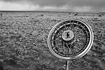 a hubcap on a barbed wire fence with the southwest desert landscape, santa fe, new mexico