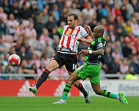 John O'Shea of Sunderland gets to the ball ahead of Andre Ayew of Swansea City during the Barclays Premier League match between Sunderland and Swansea City played at Stadium of Light, Sunderland
