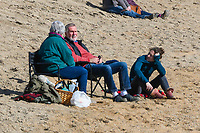BNPS.co.uk (01202 558833)<br /> Pic: Graham Hunt/BNPS<br /> <br /> Visitors not put off by the coronavirus pandemic flock to the seaside resort of West Bay in Dorset on a day of sunshine and clear blue skies.<br /> <br /> Visitors sitting on the beach.