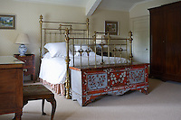 A painted chest stands at the foot of an antique brass bedstead in this guest bedroom
