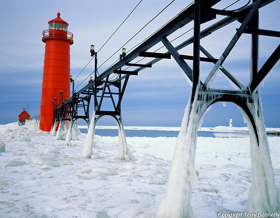 Ottawa County, MI   <br /> Grand Haven Lighthouse &amp; ice coated catwalk over the frozen surface of Lake Michigan Grand Haven State Park