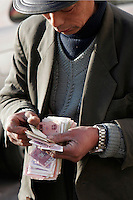 A vendor counts Chinese RMB spare changes in a Beijing street, China.