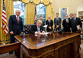 "United States President Donald Trump signs the first of three Executive Orders in the Oval Office of the White House in Washington, DC on Monday, January 23, 2017.  They concerned the withdrawal of the United States from the Trans-Pacific Partnership (TPP), a US Government hiring freeze for all departments but the military, and ""Mexico City"" which bans federal funding of abortions overseas.  Standing behind the President, from left to right: US Vice President Mike Pence; White House Chief of Staff Reince Preibus; Peter Navarro, Director of the National Trade Council; Jared Kushner, Senior Advisor to the President; Steven Miller, Senior Advisor to the President; unknown; and Steve Bannon, White House Chief Strategist.<br /> Credit: Ron Sachs / Pool via CNP"