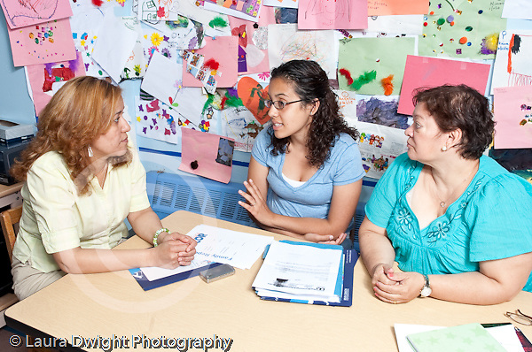 Group of three female preschool teachers conferring, meeting and talking