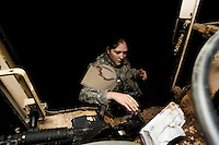 Private First Class Brenneis,  with Echo Company, 1st Battalion, 506th, 101st airborne Division grabs some tissues to clean the wind shield of her truck splashed with mud after accomplishing the first half of her mission transporting  with her unit essential equipment and supplies from FOB Corregidor to TQ Base, Al Anbar Province, Iraq on Sunday JAN 29 2006.