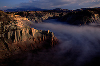 Morning fog fills a canyon below sheer sandstone cliffs of Grand Staircase?Escalante National Monument in Utah.  The rugged unique terrain of arches, plateaus and colorful canyon walls covers 1.7 million acres and was the first monument named under the BLM by President Bill Clinton in 1996.
