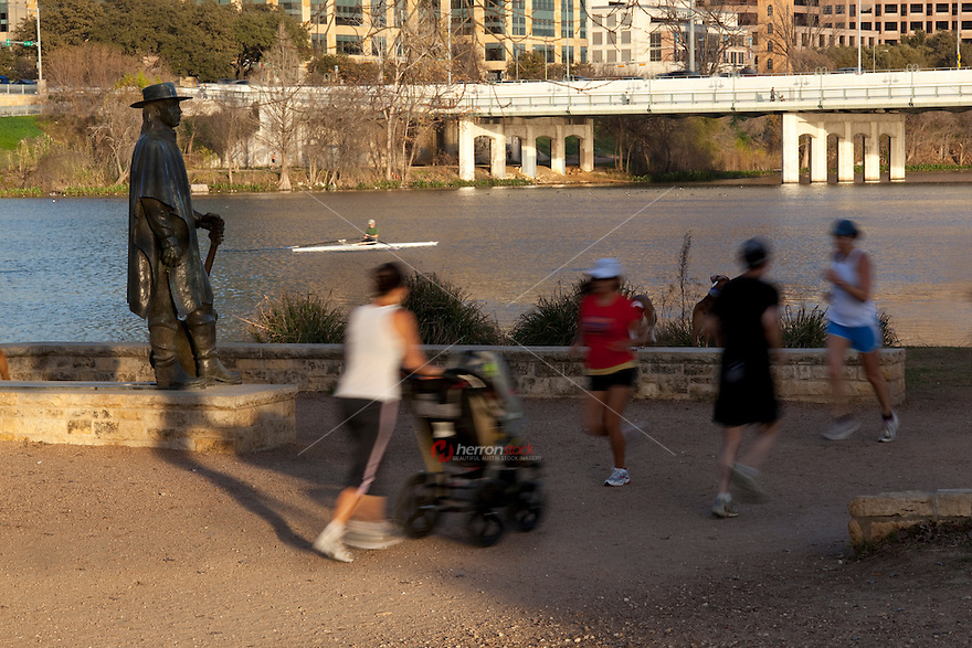 Runners and kayakers fill Lady Bird Lake hike and bike trail, a pristine location along Lady Bird Lake next to the Stevie Ray Vaughan Memorial Statue