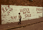 BOY WALKING ALONG STREET PASSING WALL WITH GRAFFITI STATING 'REM(EMBER)1690', 'U.V.F.', 'ULSTER NOT FOR SALE' & 'PAISLEY FOR EVER', IN BELAST,