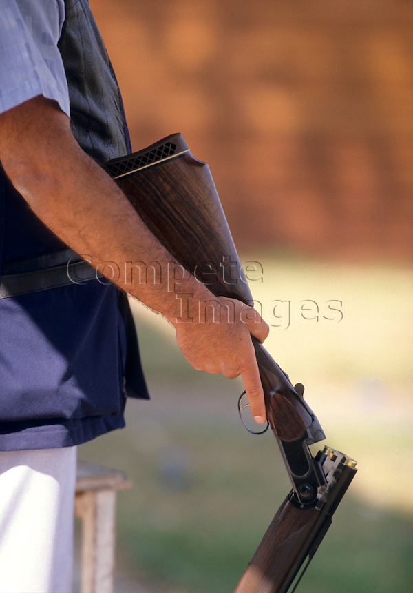 Man holding a loaded open shotgun