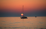 Summer sunset through a sailboat on a calm lake