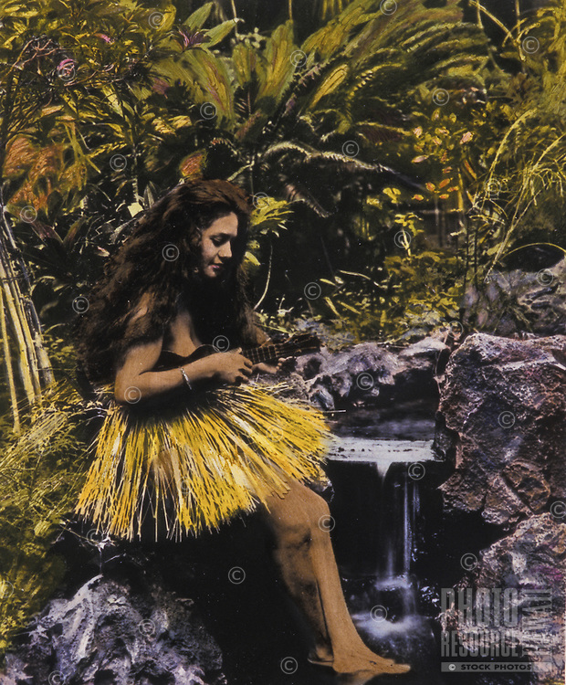 Hand-tinted historical photo of a Hawaiian hula dancer playing her ukulele near a stream