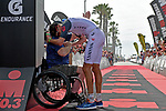OCEANSIDE, CA - APRIL 7:  Jan Frodeno of Germany hugs Ironman Challenged Athlete David Rozelle, who lost part of his leg while serving in Iraq, at the finish line for the win and new course record during the IRONMAN 70.3 Oceanside Triathlon on April 7, 2018 in Oceanside, California. (Photo by Donald Miralle for IRONMAN)