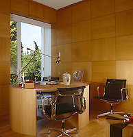 A contemporary wood-panelled study has a circular wooden desk with a suede top