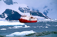 Icebreaking vesel among mountains & glaciers in Russian boat at Antarctica Peninsula.