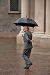 A man wearing a grey suit and smoking a cigar, walks through Piazza San Carlo in the rain in Turin, Italy