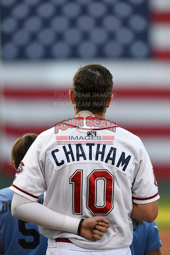 C.J. Chatham (10) stands at attention as soldiers unfurl an American flag over the left field wall before the Greenville Drive's home opening game against the Rome Braves on Thursday, April 12, 2018, at Fluor Field at the West End in Greenville, South Carolina. Greenville won, 14-4. (Tom Priddy/Four Seam Images)